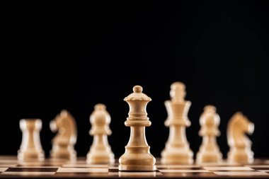 selective focus of beige wooden queen on chessboard isolated on black