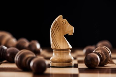close up of chessboard with scattered wooden figures and knight isolated on black