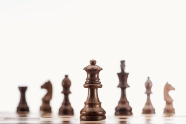 selective focus of brown wooden queen on chessboard isolated on white