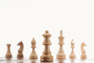 selective focus of beige wooden queen on chessboard isolated on white