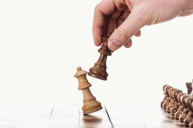 partial view of man holding brown queen near beige queen on wooden chessboard isolated on white