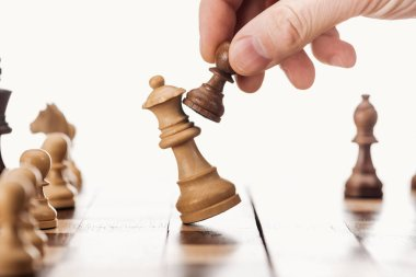 partial view of man doing move with brown pawn on chessboard isolated on white