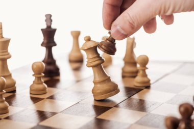 partial view of man doing move with brown pawn on wooden chessboard isolated on white