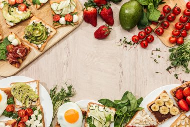 top view of toasts with vegetables, fruits and prosciutto with greenery and ingredients on wooden table