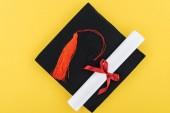 Pohled shora akademické čepice a diplom s červenou stužkou izolované na žluté