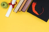 Top view of books, apple, academic cap and diploma on yellow surface