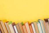 Světlé barevné knihy s temné stránky izolované na žluté