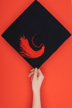 Cropped view of woman holding academic cap on red