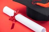 Akademické čepice se střapcem a diplom s mašlí na červené ploše