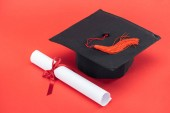 Photo Academic cap with tassel and diploma with ribbon on red surface