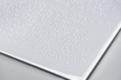 close up view of braille text on white paper isolated on grey