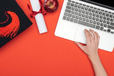 Cropped view of girl with academic cap, diploma and apple using laptop on red surface stock vector