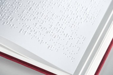 close up view of book with braille text isolated on grey