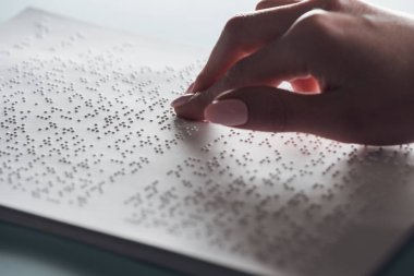 cropped view of young woman reading braille text on white paper