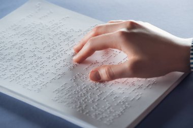 close up view of young woman reading braille text with hand