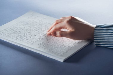 cropped view of young woman reading braille text with hand on blue