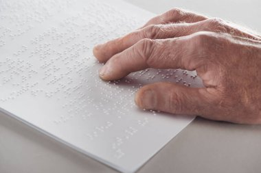 close up view of senior man reading braille text isolated on grey
