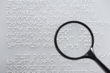 top view of braille text on white paper with magnifying glass