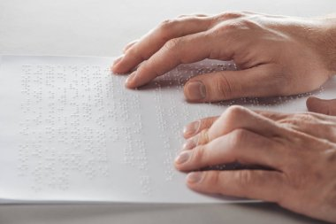cropped view of man reading braille text with hands isolated on grey