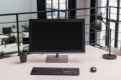 moderní pracoviště s počítačem, káva s sebou a lampy v úřadu