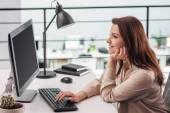 Fotografia happy young woman typing on computer keyboard at workplace in modern office