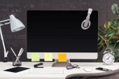 Fotografia workplace with headphones and empty sticky notes on computer monitor, lamp and stationery on white table