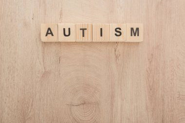 top view of autism lettering made of cubes on wooden table
