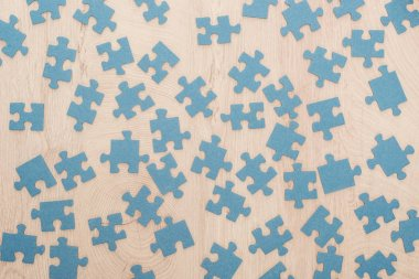 top view of blue puzzle parts scattered on wooden table