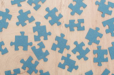 top view of blue puzzle pieces scattered on wooden table