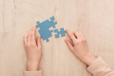 partial view of female hands with blue puzzles on wooden table