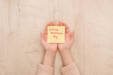 Cropped view of female hands and sticky note with red autism awareness day handwritten lettering stock vector