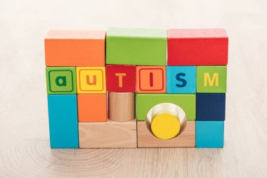 Autism lettering made of colorful building blocks on wooden surface stock vector