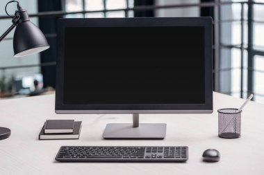 computer monitor with blank screen and stationery at workplace