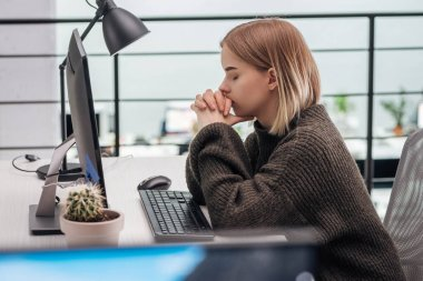 selective focus of upset girl sitting at workplace with clenched hands and closed eyes in modern office