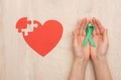 částečný pohled na ženu držící zelenou stuhu a papírové srdce na dřevěné pozadí