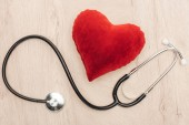 pohled na světlé srdce z hraček a stetoskop na dřevěném pozadí