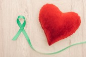 Fotografie top view of bright toy heart and green ribbon on wooden background