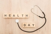 top view of cubes with health day lettering and stethoscope on wooden background