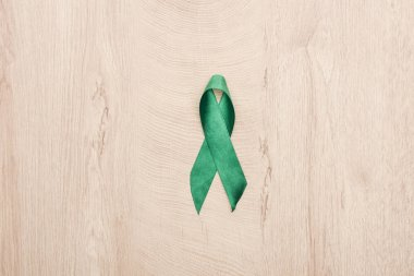 Top view of green ribbon on wooden background with copy space stock vector