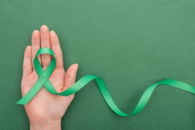 Cropped view of woman holding green ribbon on green background with copy space stock vector