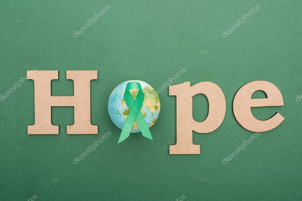 Top view of wooden word hope, toy earth and green ribbon on colorful background stock vector