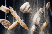 flour falling at fresh baked bread, baguettes and croissant hanging on ropes on black background