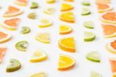 Fotografie Juicy fresh sliced citrus fruits on white surface