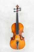 Fotografie Blick auf klassisches Cello auf grau strukturiertem Hintergrund