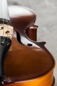 Fotografie Nahaufnahme des klassischen hölzernen Cello auf grauem, strukturiertem Hintergrund