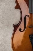 Fotografie Blick auf klassisches Cello auf grau strukturierter Oberfläche