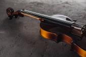 Fotografie Klassisches Violoncello aus Holz in der Dunkelheit auf strukturierter Oberfläche