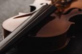 Nahaufnahme von Streichern auf Violoncello in Dunkelheit auf grau strukturiertem Hintergrund