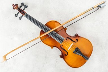 top view of classical cello with bow on grey background