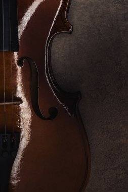 top view of classical cello on grey textured surface in darkness